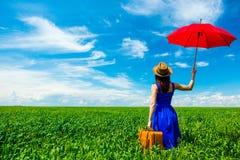Молодая женщина с чемоданом и зонтиком стоковое фото rf