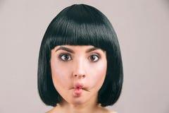 Молодая женщина с черными волосами представляя на камере Странная модель брюнета с качается стрижка Держащ губы совместно Глаза с стоковая фотография