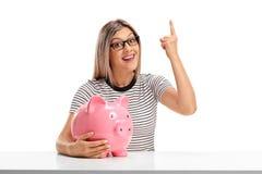 Молодая женщина с piggybank указывая вверх Стоковые Фото