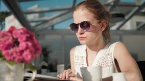 Молодая женщина с ponytail и солнечными очками выпивает кофе в ресторане акции видеоматериалы