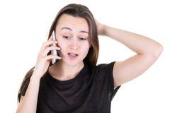 Молодая женщина удивила говорить по телефону на желтой предпосылке стоковое изображение