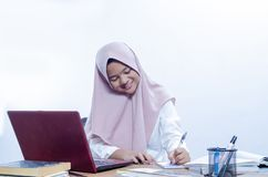 Молодая женщина улыбки уверенная работая в ее офисе стоковые фото