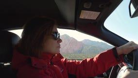 Молодая женщина управляет автомобилем на солнечный день видеоматериал
