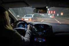 Молодая женщина управляя автомобилем на ноче стоковые изображения rf