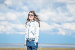 Молодая женщина усмехаясь посреди оранжевой лужайки, она смотрит камеру, настолько беспечальную облака покрыли степь неба ландшаф Стоковое Изображение RF