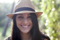 Молодая женщина усмехаясь с шляпой стоковое фото rf