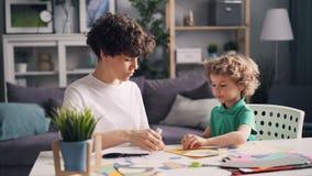 Молодая женщина уча, что ее маленький сын сделал бумажный коллаж на таблице дома акции видеоматериалы