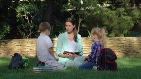 Молодая женщина учителя держит outdoors урока для мальчика и девушки с книгами в руках пока сидящ на траве сток-видео