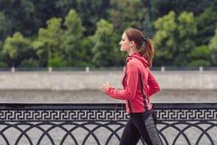 Молодая женщина фитнеса бежать в парке города стоковое изображение
