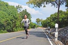 Молодая женщина фитнеса бежать на дороге горы Стоковое Изображение RF