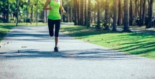 Молодая женщина фитнеса бежать на тропическом парке стоковая фотография rf