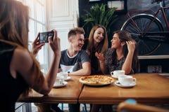 Молодая женщина фотографируя ее положительных друзей в кофейне используя smartphone, предпосылку defocused стоковое фото rf