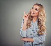 Молодая женщина фотомодели указывая вверх по ее пальцу Стоковое Фото