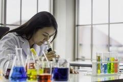 Молодая женщина химика смотря через микроскоп, работая на лаборатории, химическое испытание в лаборатории, концепция для улучшать стоковые фотографии rf