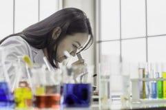 Молодая женщина химика смотря через микроскоп, работая на лаборатории, химическое испытание в лаборатории, концепция для улучшать стоковое изображение rf