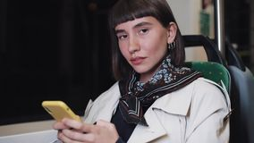 Молодая женщина хипстера смотря камеру и усмехаясь усаживание в общественном транспорте, steadicam сняла Она держа видеоматериал