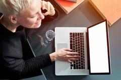 Молодая женщина хипстера с белокурыми короткими волосами усмехаясь и говоря мобильным смартфоном, работающ на ноутбуке, сидя на о стоковая фотография