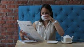 Молодая женщина читает газету над чашкой кофе в ресторане акции видеоматериалы