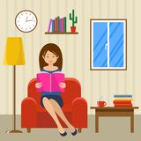 Молодая женщина читает сидеть в стуле Стоковое Фото