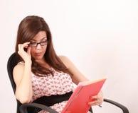 Молодая женщина читая красную кассету Стоковое фото RF