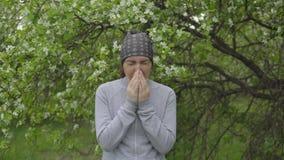 Молодая женщина чихает около яблони, аллергии сток-видео