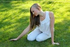 Молодая женщина штрихуя траву Стоковые Фото