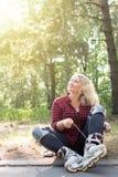 Молодая женщина blonge связывает шнурки на ее ботинках ролика стоковое фото