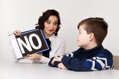 Молодая женщина brunnette говоря с мальчиком крытым белую комнату Женщина психолога с patiant Терапия психологии стоковая фотография