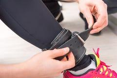 Молодая женщина buckling кожаный ремень к ее лодыжке стоковое фото