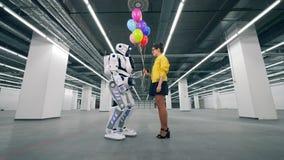 Молодая женщина gifting воздушные шары к высокорослому роботу сток-видео