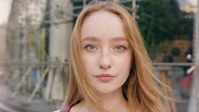 Молодая женщина redhead представляя в городке видеоматериал