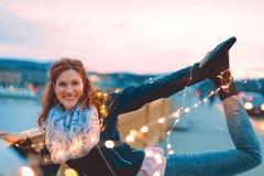 Молодая женщина redhead представляя с fairy светами outdoors teal и o Стоковое Фото