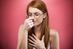 Молодая женщина Redhead сжимая ее нос над розовой предпосылкой стоковое фото rf