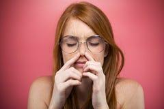 Молодая женщина Redhead сжимая ее нос над розовой предпосылкой стоковые фотографии rf
