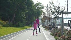 Молодая женщина Rollerblading с дочерью видеоматериал