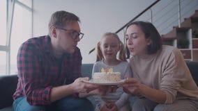 Молодая жизнерадостная дочь дует свечи на белом именнином пироге с семьей дома видеоматериал