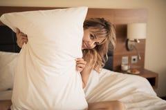 Молодая жизнерадостная женщина усмехаясь в спальне стоковые фотографии rf