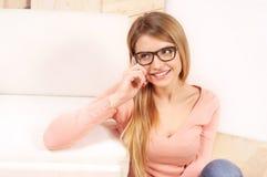 Молодая задумчивая женщина говоря на телефоне и смотря прочь дома Стоковые Изображения RF