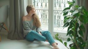Молодая задумчивая женщина сидя окном акции видеоматериалы