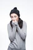 Молодая замерзая девушка на сером цвете стоковая фотография rf