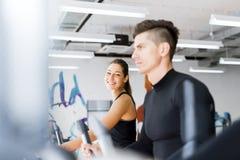 Молодая здоровая группа людей разрабатывая на эллиптическом тренере Стоковое Изображение