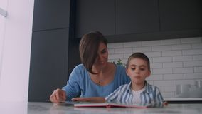 Молодая испанская мать с ее сыном сидя на таблице учит для чтения ребенка помогая и пробуждая его сына, акции видеоматериалы
