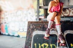 Молодая и горячая девушка сидит на верхней части места для кататься на коньках Она держит колени ее ног совместно Девушка Стоковое Фото