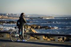 Молодая и красивая девушка едет велосипед пристанью рядом с Атлантическим океаном стоковое изображение rf