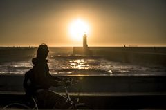Молодая и красивая девушка едет велосипед пристанью рядом с Атлантическим океаном стоковая фотография rf