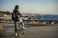 Молодая и красивая девушка едет велосипед пристанью рядом с Атлантическим океаном стоковая фотография