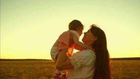 Молодая и красивая мать с ребенком играет в воздухе в слепимости захода солнца золотого солнца и смеяться над движение медленное видеоматериал