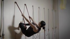 Молодая и милая дама выполняет перевернутое asana используя веревочки, приниманнсяую за дамой йогу patta на клубе акции видеоматериалы