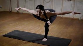 Молодая и милая женщина в костюме спорт стоит на одной ноге и делает протягивающ тренировки стоя на циновке акции видеоматериалы