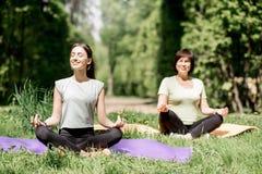 Молодая и старшая женщина делая йогу в парке Стоковые Фотографии RF